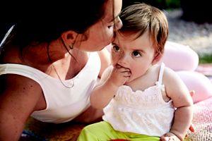 Kind hat Hand im Mund