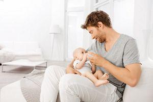 Vater füttert Baby mit Fläschchen