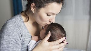 Mum Kissing Newborn On Forehead